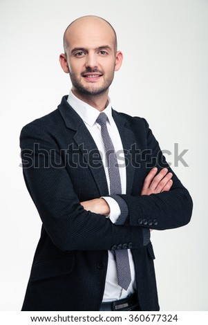 Cheerful attractive young business man standing with crossed arms over white background - stock photo
