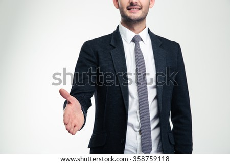 Cheerful attractive young businessman in black suit and tie giving hand for handshake over white background - stock photo