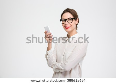 Cheerful attractive young businesswoman in glasses standing and using mobile phone over white background - stock photo
