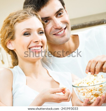 Cheerful attractive young couple eating popcorn and watching TV together