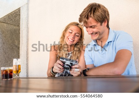 cheerful attractive young couple on a date, looking at pictures they have taken with a photo camera