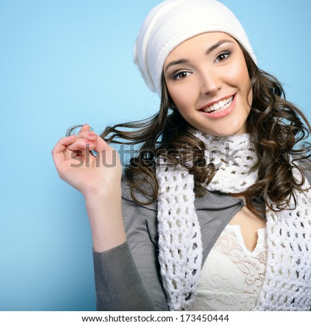 Cheerful attractive young girl smiling and looking at camera, in warm clothes