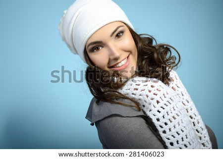 Cheerful attractive young girl smiling and looking at camera, in warm clothes and hat, toned