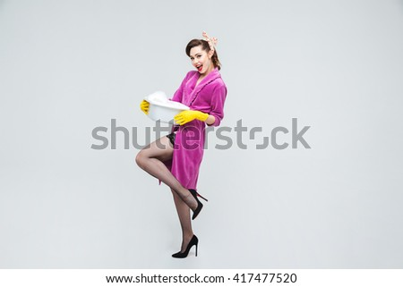 Cheerful attractive young housewife standing and holding basin with foamed detergent - stock photo