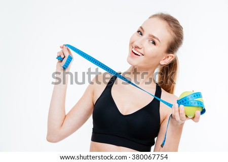 Cheerful attractive young sportswoman holding apple with blue measuring tape over white background - stock photo