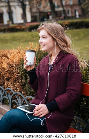 Cheerful attractive young woman drinking coffee and listening to music from tablet - stock photo