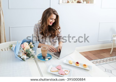 Cheerful attractive young woman drinking latte and using laptop in cafe - stock photo