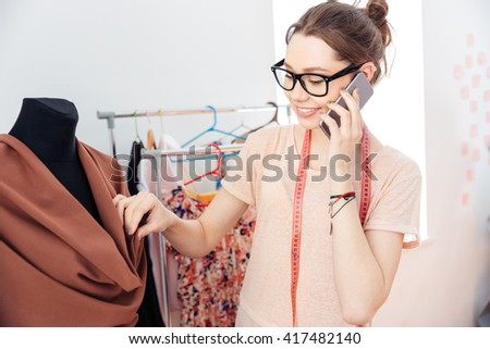 Cheerful attractive young woman fashion designer working and using smartphone  - stock photo