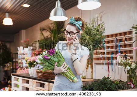 Cheerful attractive young woman florist holding two bunches of tulips and talking on mobile phone in flower shop - stock photo