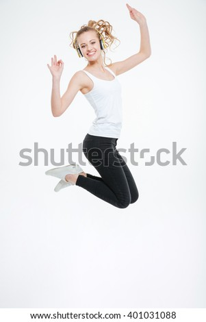 Cheerful attractive young woman listening to music with headphones and jumping in the air over white background  - stock photo