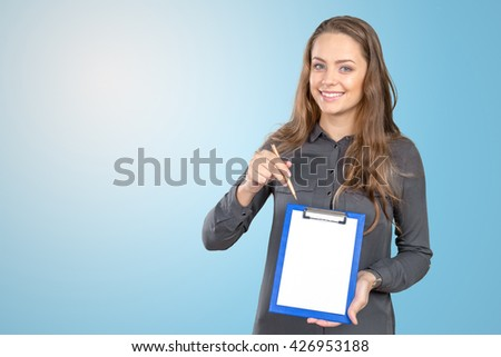Cheerful attractive young woman showing blank clipboard