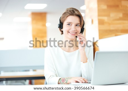 Cheerful attractive young woman sitting and working in call center with headset and laptop in office - stock photo