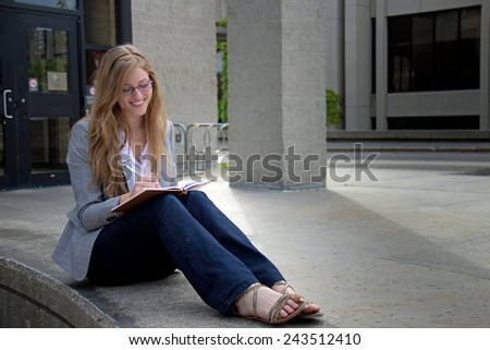 Cheerful, attractive young woman with journal - stock photo