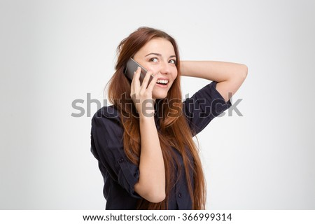 Cheerful attractive young woman with long brown hair talking on cell phone over white background - stock photo