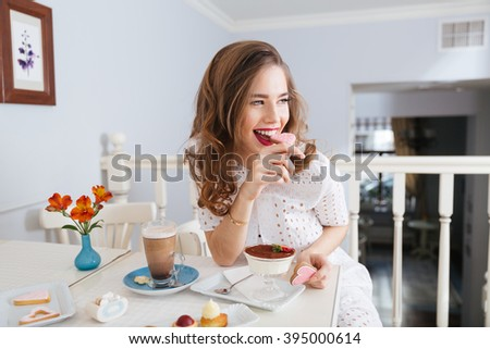 Cheerful attractive young woman with long curly hair sitting and eating heart shaped cookies  - stock photo