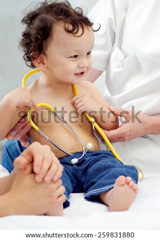Cheerful  baby at the doctor. - stock photo