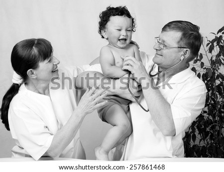 Cheerful baby at the dotcor. - stock photo