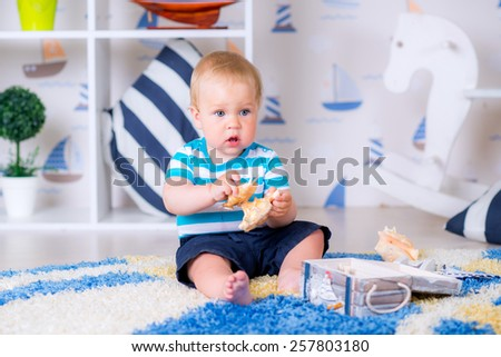cheerful baby boy playing in a bright room with a chest full of sea shell - stock photo