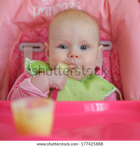 cheerful  baby child eats itself with a spoon