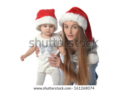 Cheerful baby girl and woman in Santa Claus hat.