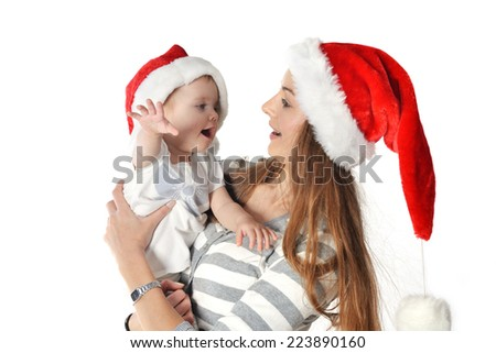 Cheerful baby girl and woman in Santa Claus hat.  - stock photo