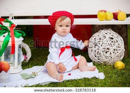 cheerful baby girl is playing on the grass - stock photo
