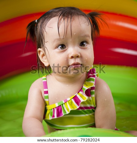 Cheerful baby girl playing in wading pool - stock photo
