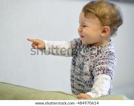 Cheerful baby girl plays on the couch at home. The one-year child points his finger.