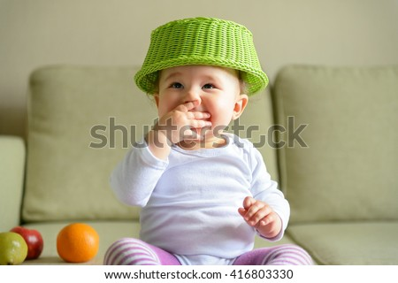 Cheerful baby girl plays with dish and fruit at home - stock photo