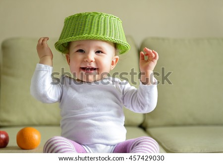 Cheerful baby girl plays with dish and fruit at home. A child holds up his hands. - stock photo