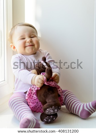 Cheerful baby girl plays with toy bear at window at home - stock photo