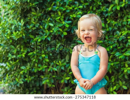 Cheerful baby girl wet after swimming pool on a background of green bushes - stock photo