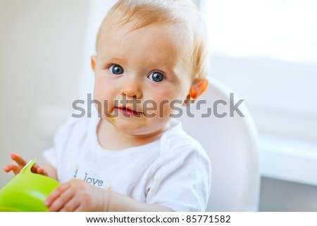 Cheerful baby  sitting in baby chair