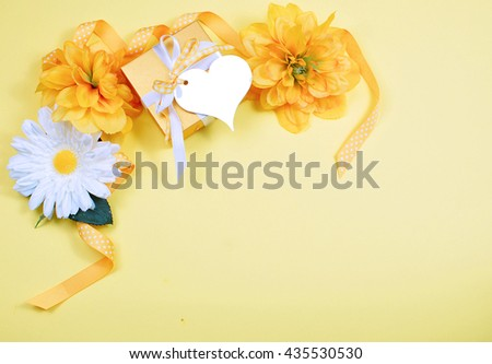Cheerful background border on creamy yellow background includes yellow and white silk flowers, polka dot ribbon, golden gift box with blank, heart shaped tag for your text. Copy space. - stock photo