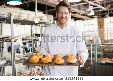 Cheerful baker holding tray of bread at the bakery - stock photo