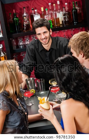 Cheerful barman chatting with young friends at cocktail bar - stock photo