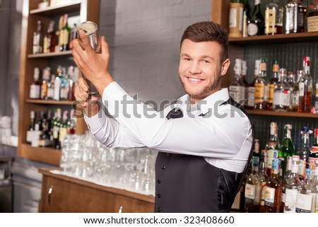 Cheerful barman is standing near alcohol drinks in bar. He is holding a shaker and mixing drink. The man is looking at camera and smiling - stock photo