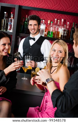 Cheerful barman prepare alcoholic cocktail young friends at the bar - stock photo