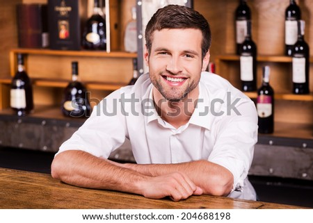 Cheerful bartender. Handsome young male bartender in white shirt leaning at the bar counter and smiling - stock photo