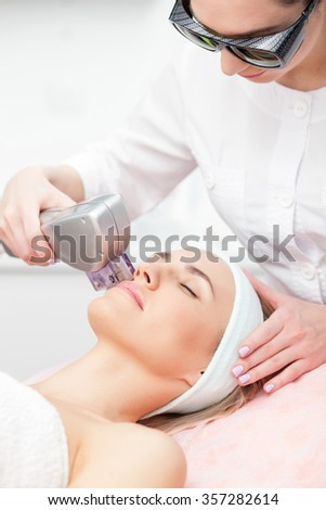 Cheerful beautician is undergoing laser treatment for female face. She is standing and wearing goggles. The woman is lying and relaxing. She closed her eyes with enjoyment - stock photo