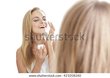 cheerful beautiful blonde woman while  applying some facial cream on her nose isolated on white background - stock photo
