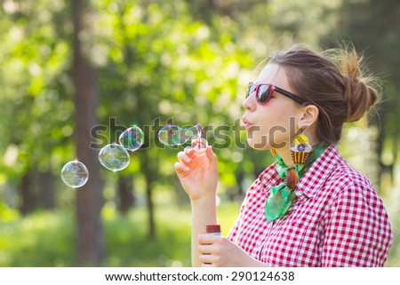 Cheerful beautiful brunette girl blowing soap bubbles outdoor.