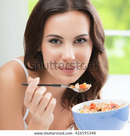 Cheerful beautiful brunette woman eating muslin, indoors.  - stock photo