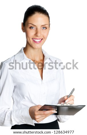 Cheerful beautiful business woman with clipboard writing, isolated over white background