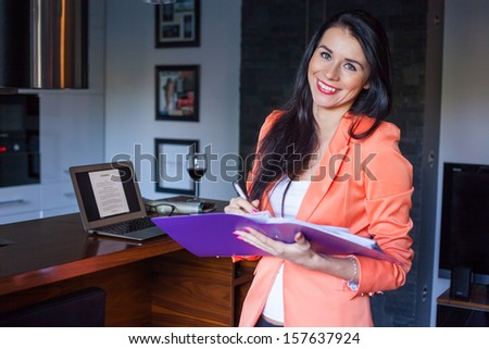 Cheerful beautiful businesswoman holding notebook .