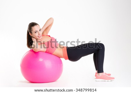 Cheerful beautiful fitness girl training abdominal muscles using fitball isolated over white background