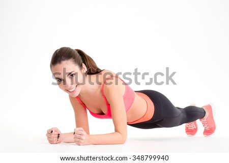 Cheerful beautiful fitness woman in sportwear doing plank exercise over white background - stock photo