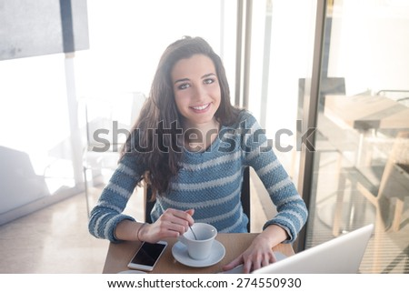 Cheerful beautiful girl at the cafe having a coffee and using a laptop