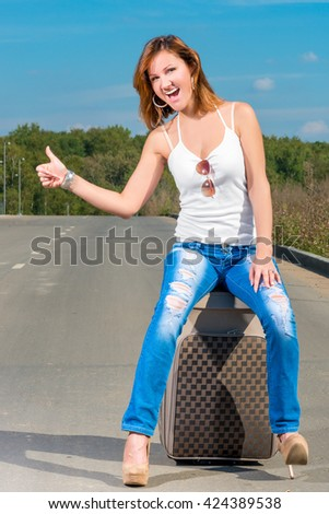 cheerful beautiful girl catches a passing car - stock photo