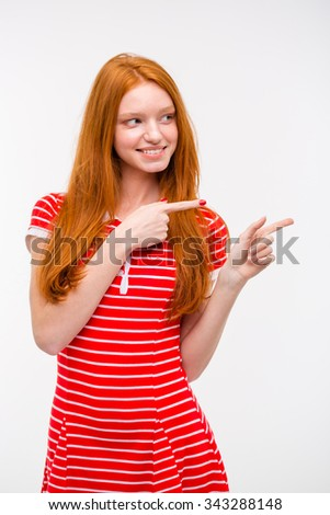 Cheerful beautiful happy young redhead woman in red striped dress pointing away while standing against white background - stock photo